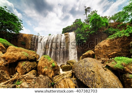Bottom view of waterfall with crystal clear water among green woods on dramatic sky background in Vietnam. Summer forest landscape. The Elephant waterfall is a popular tourist destination of Asia. - stock photo