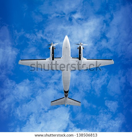 Bottom view - twin prop cargo plane on sky background - stock photo