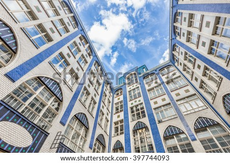 Bottom wide angle view of historic inner courtyard with beautiful facade at famous Hackesche Hofe building complex with blue sky and clouds, district of Spandauer Vorstadt, central Berlin, Germany - stock photo