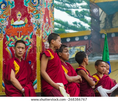 BOUDANATH, NEPAL - MAY 3: Tibetan monks wait stand in line during a Buddhist ritual. - stock photo