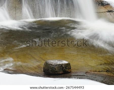 Boulder below winter cascade of waterfall. Wavy water level.. Stream in deep freeze.  - stock photo