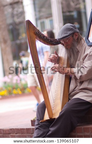 BOULDER, CO - MAY 18, 2013:  Street musician playing classical harp to entertain tourists on the Pearl Street Mall in Boulder, CO on May 18, 2013. - stock photo