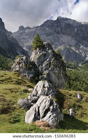 Boulder with wayside shrine and wooden bench at the pasture of Stegmoosalm, mountain Hochkoenig, Berchtesgaden Alps, Salzburg, Austria - stock photo