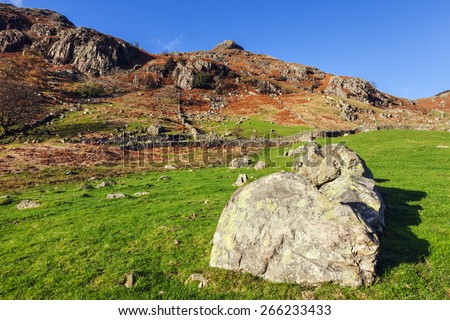 Boulders and the Pikes. Massive boulders lie in a field in front of the prominent Langdale Pikes. - stock photo