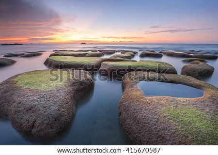 boulders of rocks with green moss seascape sunset view at tindakon dazang Beach Kudat Malaysia. Image may contain soft focus due to long exposure time, - stock photo