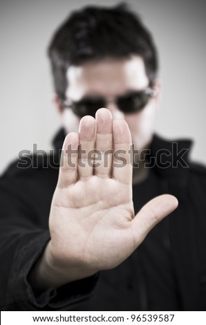 Bouncer in glasses makes stop gesture - stock photo