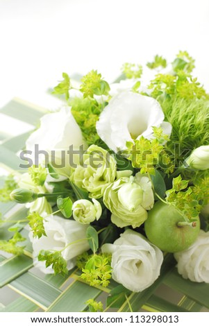 Bouquet from different white seasonal flower and green in basket - stock photo