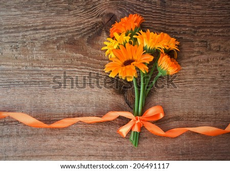 Bouquet from flowers of calendula with orange satin ribbon on wooden background - stock photo