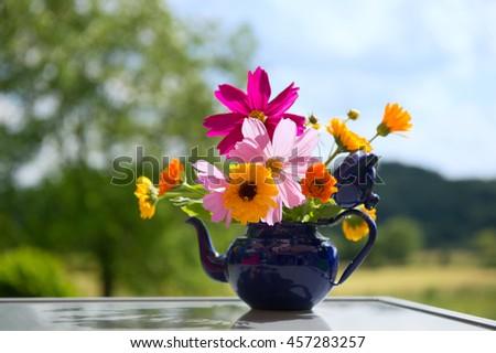 Bouquet garden flowers in blue tea pot - stock photo