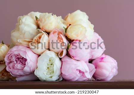 Bouquet made of artifical pink peony laying on a  wood surface. Shot against pink wall background. Shallow DOF. - stock photo