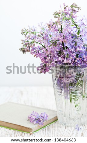 Bouquet of a lilac in a vintage vase and old book - stock photo