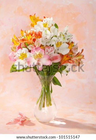 Bouquet of Alstroemeria  in a transparent glass vase on abstract background - stock photo