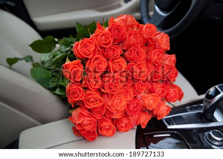 bouquet of beautiful red roses in luxury car. Composition for a romance or anniversary - stock photo