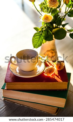Bouquet of beautiful roses with a cup on the books in vintage style - stock photo