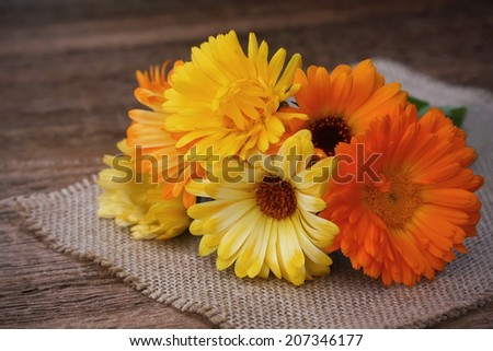 Bouquet of calendulas on canvas on old wooden background - stock photo