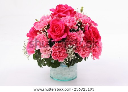 Bouquet of carnation and rose flowers in glass vase isolated on white background - stock photo