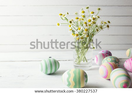 Bouquet of chamomiles in a glass vase and easter eggs in pastel color on white wooden table - stock photo