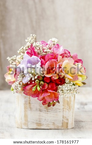 Bouquet of colorful freesia flowers in wooden shabby chic box. Copy space - stock photo