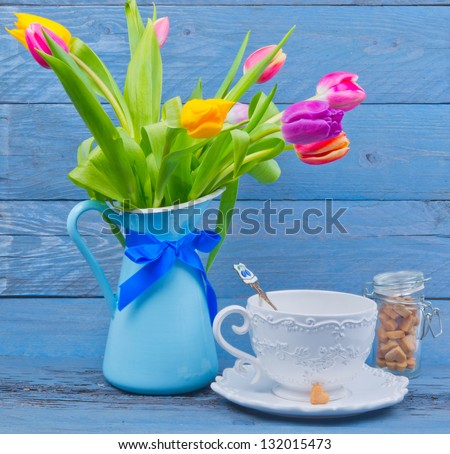 Bouquet of colorful tulips in a blue jug, next cup of tea on blue wooden table - stock photo