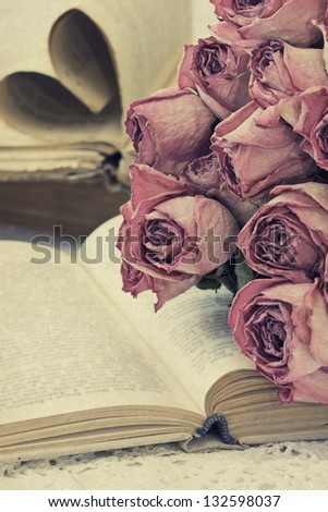 bouquet of dried roses on the old book in a vintage style - stock photo