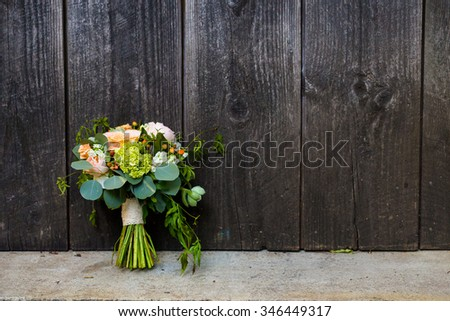 Bouquet of flowers for the bride on her wedding day paired with a wood backdrop. - stock photo