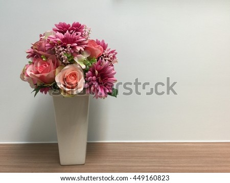 Bouquet of flowers in vase on wooden table in front of white wall background with copy space. - stock photo