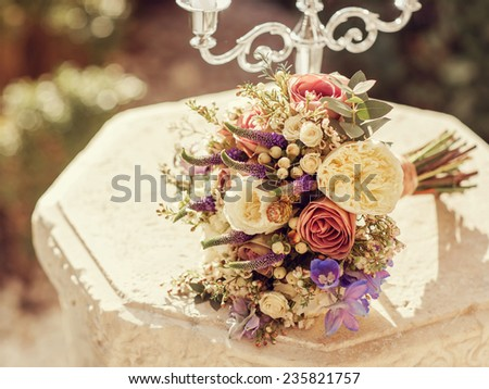 Bouquet of flowers lying on a stone table with a candlestick outdoors. - stock photo