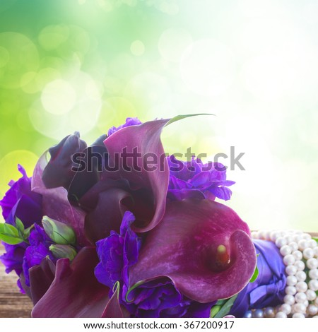 Bouquet of fresh calla lilly and eustoma flowers close up on wooden table with green background - stock photo