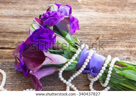 Bouquet of fresh calla lilly and eustoma flowers with pearls  on wooden table  - stock photo