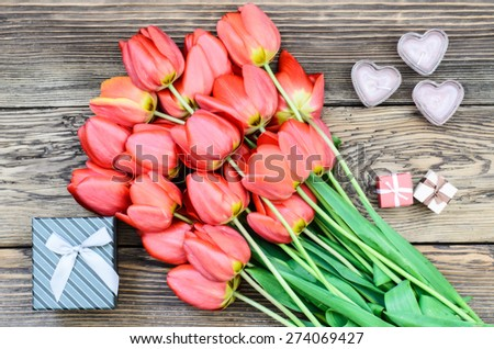 Bouquet of fresh colorful red tulips with a decorative three gift lying on a rustic wooden background symbolic of an anniversary, Valentines Day and love, overhead view - stock photo