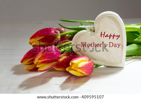 Bouquet of fresh tulips in red yellow and a wooden heart, love decoration, sample text Happy Mothers Day, selected focus and copy space - stock photo