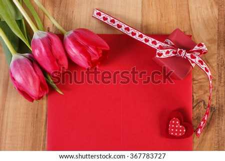 Bouquet of fresh tulips, love letter in envelope, wrapped gift and red heart, decoration for Valentines Day, copy space for text - stock photo