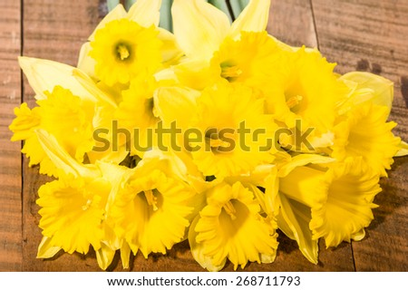 Bouquet of fresh yellow daffodils on wooden table - stock photo