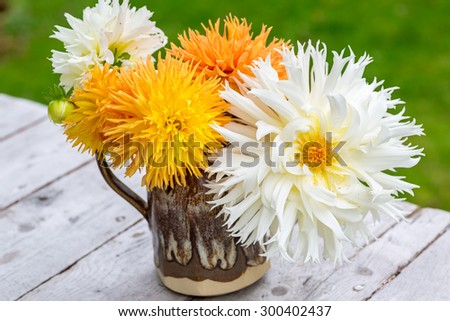 Bouquet of  home grown dahlias in a pottery pitcher. - stock photo
