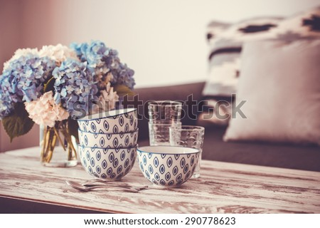 Bouquet of hortensia flowers and glass bowls on modern wooden coffee table and cozy sofa with pillows. Living room interior and home decor concept. Toned image - stock photo