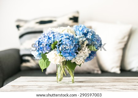 Bouquet of hortensia flowers on modern wooden coffee table and cozy sofa with pillows. Living room interior and home decor concept - stock photo
