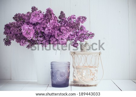 Bouquet of lilac flowers in vintage vase and decorative candlestick on a white wooden board, wedding decoration in a rustic style - stock photo