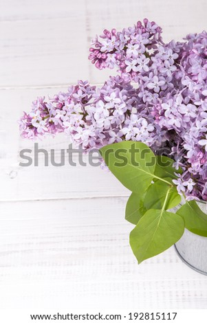 bouquet of lilac flowers on white wooden background - stock photo