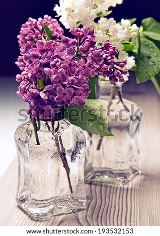 Bouquet of lilac in a vase on wooden table - stock photo