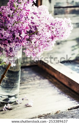 Bouquet of lilac spring flowers on wooden background. - stock photo