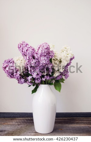 Bouquet of lilacs in a glass vase near books and candle. Lilac flowers in vintage style against white background. - stock photo