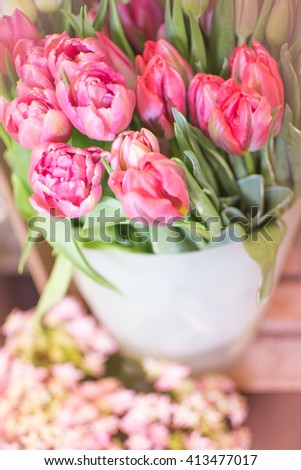 Bouquet of magenta pink tulips (Tulipa gesneriana) on rustic wooden chair in front of a flower shop - Happy Mothers Day or Valentine Card - stock photo
