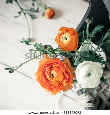 Bouquet of orange and white ranunculus in wooden box, on white wooden background, overview. Vintage toned photo. - stock photo