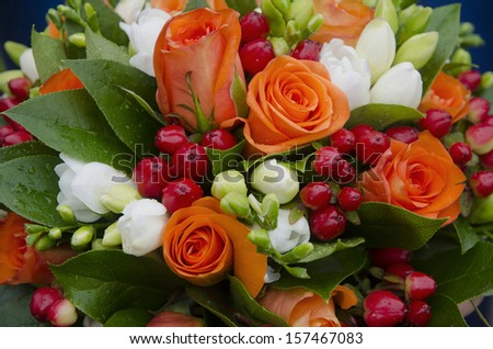 bouquet of orange and white roses decorated with berries with drops of dew - stock photo