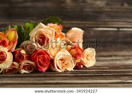 Bouquet of orange roses on brown wooden background - stock photo