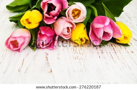 bouquet of pink and yellow tulips  on a wooden background - stock photo