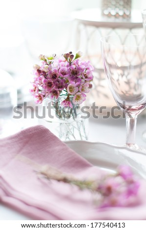 Bouquet of pink flowers on a festively decorated table, a bright summer table decor. - stock photo