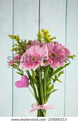 Bouquet of pink gerbera flowers  and a toy heart for Valentine's day on light blue wooden background. - stock photo