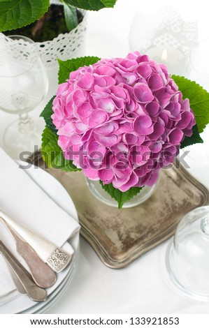 Bouquet of pink hydrangeas and vintage cutlery on the festive table closeup - stock photo
