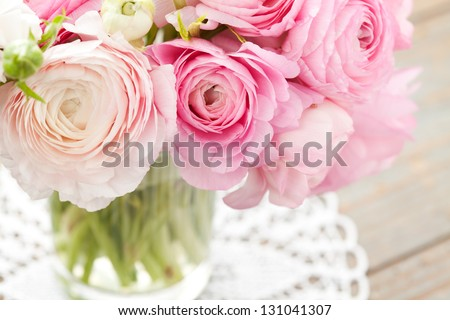 Bouquet of pink ranunculus in vase on wooden background - stock photo